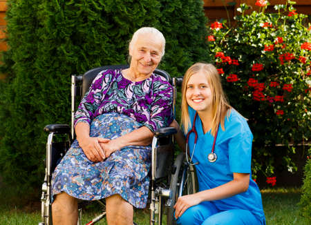 cares: Kind doctor taking care of elderly woman at the nursing home. Stock Photo