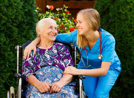 Supporting young doctor with elderly patient at the nursing home.