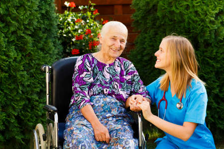 Contented old woman with her kind doctor at the nursing home. Stock Photo