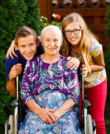 Teenager grandchildren visiting their old disabled grandmother. photo