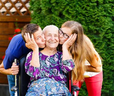 personas abrazadas: Abuela contento de ser amado y besado por hermosos nietos.