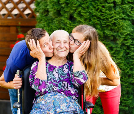 people teenagers: Contented grandmother being loved and  kissed by beautiful grandchildren.