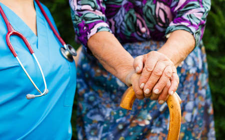 parkinson's disease: Doctor supporting elderly patient with Parkinsons disease.