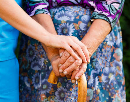 Doctor giving a supporting hand for elderly disabled woman.