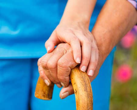 Supporting hand from doctor for elderly with parkinsons disease. photo