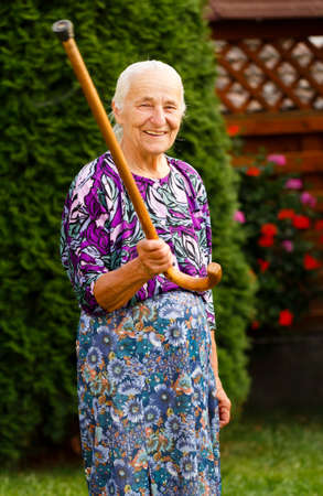 garden staff: Funny grandmother threatening with her walking stick. Stock Photo