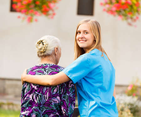 carer: Young kind doctor helping old lady on a walk in the garden.
