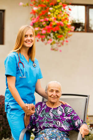 Elderly patient being supported by young female doctor. Stock Photo