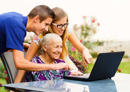 Old grandmother using successfully the modern technology. Stock Photo