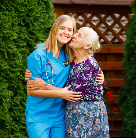 homecare: Lovely patient being pleased with homecare services, kissing her doctor.
