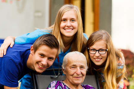 Beautiful grandchildren visiting grandmother at the nursing home. Stock Photo
