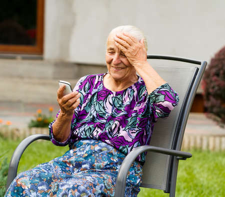 Funny grandmother confused with using smartphone. photo