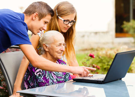in loving memory: Grandson showing something to grandma on the computer.