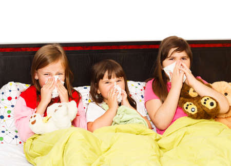 Sick little girls suffering from bad influenza, staying in bed.