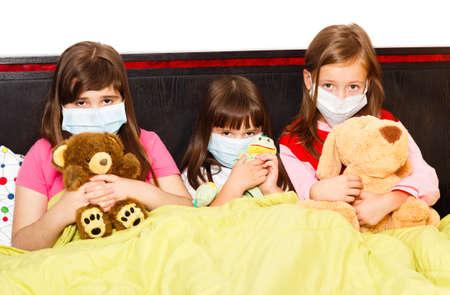 niños enfermos: Los niños enfermos en la cama con máscaras médicas debido a la infección con el virus de la influenza.