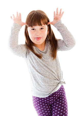 protrude: Childish disrespectful gesture from adorable little girl with tongue out. Stock Photo