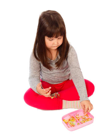 banding: Cute little girl being busy with handicraft, making colourful loom bands.