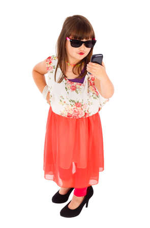 imitating: Trendy little girl imitating adults, taking duck face selfie in studio. Stock Photo