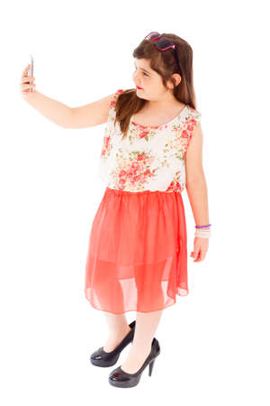 imitating: Little girl knowing how to take a good selfie, posing well.