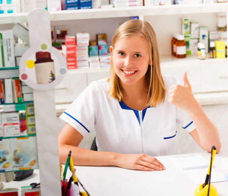 contented: Young kind pharmacist being contented with her occupation.