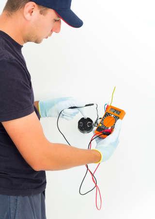 Handsome electrician measuring voltage in current outlet.