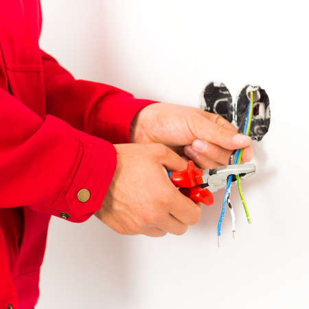 mounting: Electrician working with wires, mounting new electrical outlet.