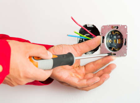 mounting: Male hand mounting new electrical outlet on wall. Stock Photo