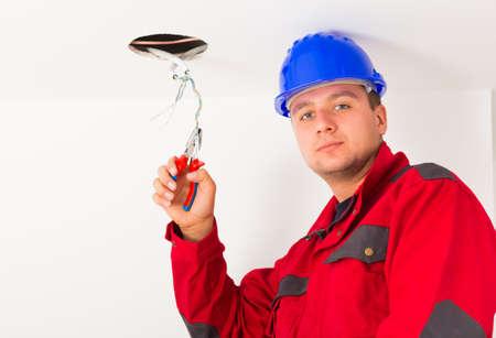 ingeniero electrico: apuesto ingeniero de montaje nuevo oultlet eléctrica en el techo.