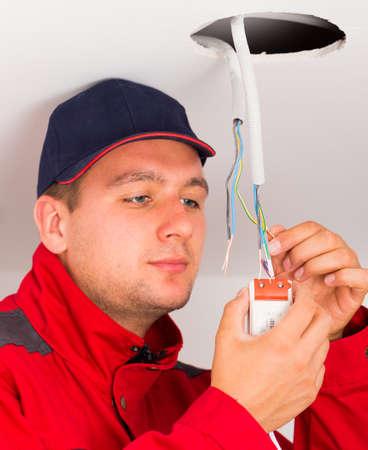 Montage: Sch�ne Elektriker in Schutzkleidung Montage Deckenbeleuchtung. Lizenzfreie Bilder