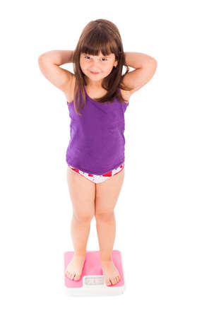 obesity kids: Little cutie being worried of her outlook, standing on a scale.