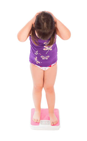 embarassed: Little girl being lost because of the weight she gain. Stock Photo