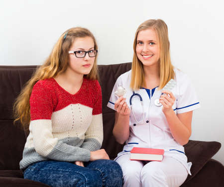 gynecologist: Gynecologist helping teenager with information on contraception.