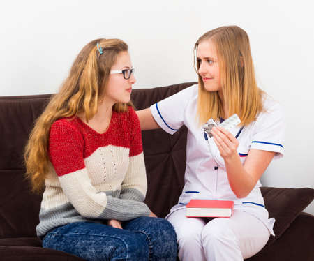 gynecologist: Gynecologist giving useful advice to teenager on contraception.