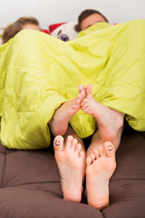Sexy time concept - smiley kissing toes in bed. Stock Photo