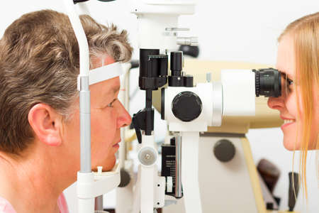 Young doctor and middle-aged patient during sight examination.