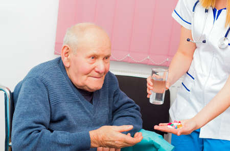 Nursing home assistant giving daily treatment to patient with Alzheimer Stock Photo