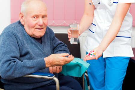 kindness: Elderly man in wheelchair taking several medications from kind nurse.