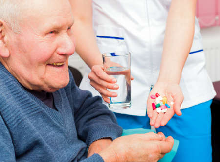 Smiling senior man taking daily treatment at the nursing home, being happy about it. Stock Photo