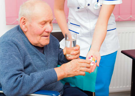 taking medicine: Hospital services for elderly in wheelchair, young nurse helping senior patient. Stock Photo