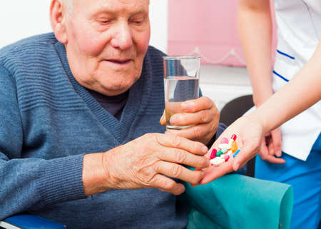 carer: Senile elderly man taking daily medicine at the nursing home.