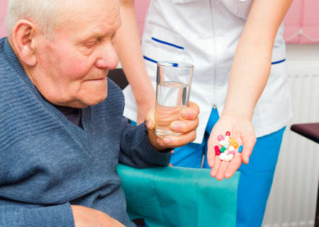 Elderly man in wheelchair taking several medicine from kind nurse.