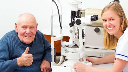 man thumbs up: Happy senior man with presbyopia at an optical examination Stock Photo