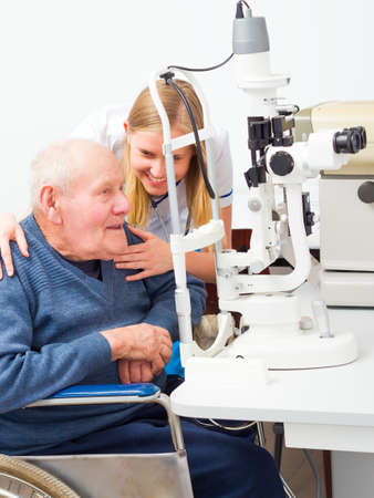 senile: Young helpful doctor with senile elderly patient at an optical exam. Stock Photo