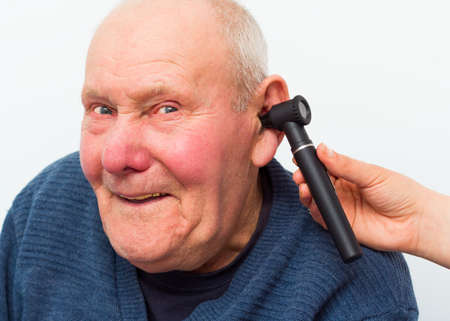 Elderly patient with dementia, making fun at the otolaryngology during medical examination.