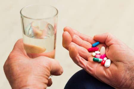personas tomando agua: Problemas de salud en la vejez, tomando varios medicamentos.