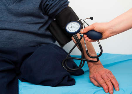 investigated: Old disabled man being investigated by cardiologist, measuring blood-pressure. Stock Photo