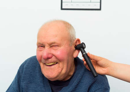 eustachian: Happy patient at the otolaryngology, making fun with doctor during examination with auroscope.