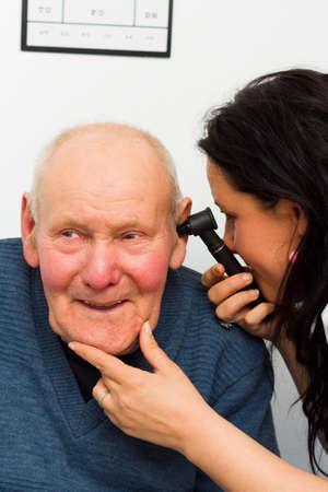 eardrum: Smiling patient enjoying hearing examination with otoscope.