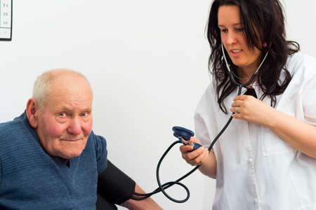 elderly patient: Elderly patient at the cardiology - doctor measuring his blood-pressure.