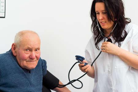 enfermera con paciente: Paciente mayor en la cardiolog�a - m�dico que mide su presi�n arterial.